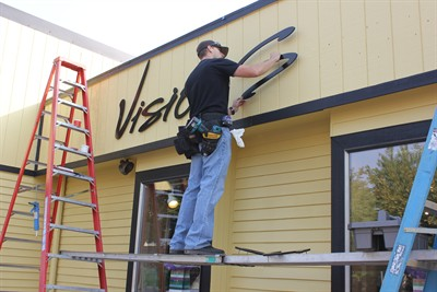 by: Photo by Tony Ahern - Brandon Searcy, of Impact Graphics, puts up a new sign at Vision Source in downtown Madras. Owner, optometrist Jessica Tegen, had the building painted an eye-catching vivid yellow with black trim, with help from the MRC grant.