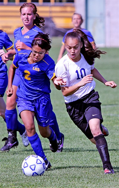 by: Bily Gates/The Pioneer - Madras sophomore Mariah Stacona blows past a Lakeview defender on her way to the goal during the Buffs' 2-1 victory against the Honkers on Saturday in Madras. Stacona started the match as the Buffs' goalkeeper, then was moved to forward, where she scored both goals.