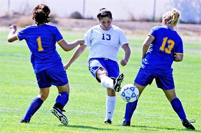 by: Bily Gates/The Pioneer - Madras junior Alicia Farias splits a pair of Lakeview defenders with a pass during the Buffs' 2-1 win against the Honkers on Saturday in Madras. The win is Madras' second of the year, one more than their win total for all of last season.