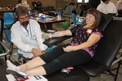 by: Photo By Susan Matheny - Red Cross medical assistant Mark Vieu prepares to collect the 100th unit of donated blood from Culver teacher Cindy Dix, Sept. 27. Dix has gotten to know Vieu and several other Red Cross workers during her many visits to donation sites over the years.