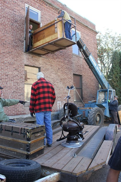 by: Photo by Billy Gates - A glass case is lowered from the second floor with a hydraulic lift to join an old trunk and dentist's chair on the trailer.