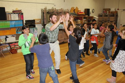 by: Photo by Susan Matheny - Joe Baumann uses reel-type dances to teach singing and rhythm to a class of third-graders at Metolius Elementary.