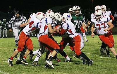 by: Billy Gates/The Pioneer - A herd of Madras White Buffalos tackle Estacada running back Brandon Beck during a Tri-Valley Conference football game Friday night in Madras. The Buffs kept the Rangers' running game from breaking big plays to win, 28-7, and claim a home playoff game this Friday against rival Crook County.