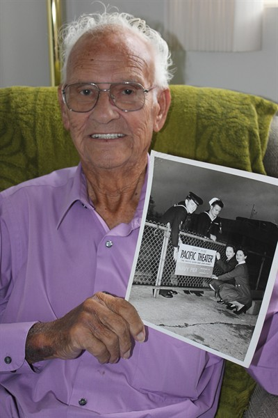by: Photo By Susan Matheny - World War II veteran Earl Sears holds a photo he was asked to pose for to help advertise war bonds. In the photo, he is in the white cap.