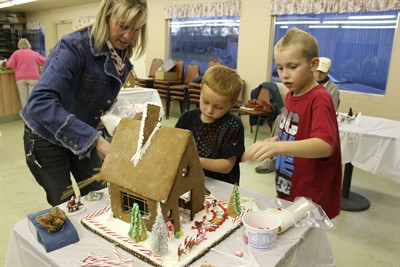 by: Photo By Susan Matheny - Mom Ronica Comingore helps sons Conner, 8, and Chase, 6, decorate their gingerbread house.