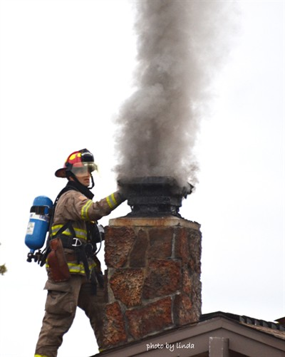 by: Photo by Linda Larson - A firefighter checks the smoke billowing out of a chimney fire in this undated photo.
