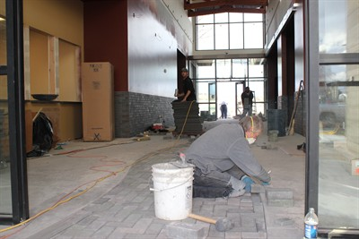 by: Photo by Holly M. Gill - A crew from Kevin Spencer Masonry, of Bend, installs the pavers that run through the lobby and out the front door of the new Madras City Hall-Police Station. The facility is expected to be completed by the end of the month.