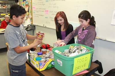 by: Photo by Susan Matheny - Jefferson County Middle School sixth-graders Josiah Washington, left, Richayla Elliott, and Elaina Nambo stack cans donated to the food drive. Teacher Margee O'Brien is in the background.