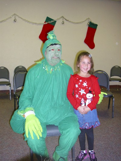 by: Submitted Photo - The Grinch visits with Elise at the library's Christmas Fun event.