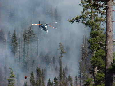 by: Contributed - A helicopter prepares to make a drop on the Link Fire Monday.