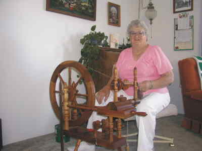 by: Photo By Susan Matheny - Luella Friend twists yarn at her spinning wheel.