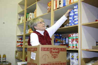 by: Photo By Susan Matheny - Food Bank Director Brenda Curnutt fills a box on Tuesday.