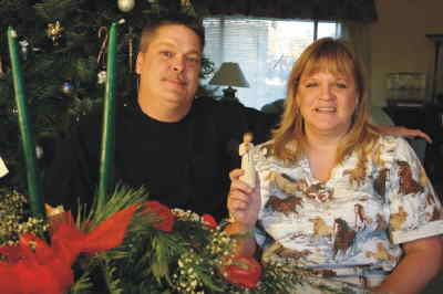 by: Photo By Holly M. Gill - Ron and Jennifer Thompson display flowers and angel sent by Kenyons.