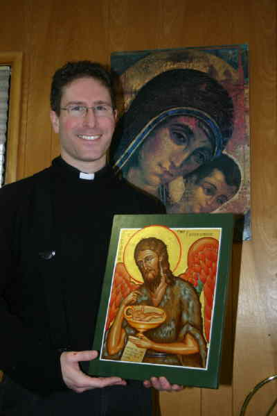 by: Photo By Susan Matheny - Father Andrew Colvin has a collection of religious lcons, and wrote the icon of St. John the Baptist he is holding.