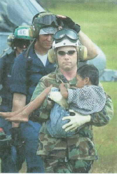 by: Associated Press Photo - Lt. Shawn Harris carries an Indonesian boy off the USS Shoup to medical facilities at the Banda Aceh airport in Indonesia.