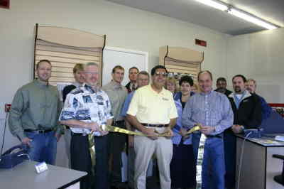 by: Photo By Tony Ahern - Manager Bob Serrano, center, cuts the ribbon to open the new shop, with Chamber Director Parrish Van Wert at left adn Madras Mayor Rick Allen at right. The business is a Unicel agent.