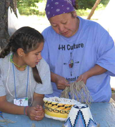 by: Photo By Peg Herring - Myra Johnson helps a young camper weave a basket during 4-H Culture Camp.