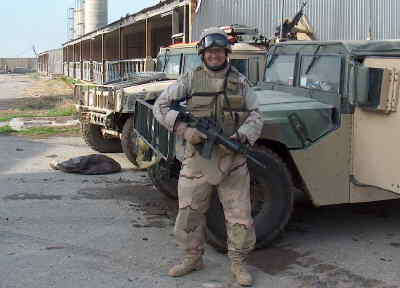 by: Submitted Photo - Sgt. England in Iraq ready for work with his M-4 rifle, body armor and a Kevlar helmet.