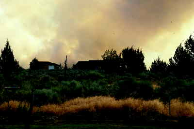 by: Photo By David Jones - Smoke hovered over homes during the early stages of the Geneva III fire last week. Before it was corraled, the fire charred 480 acres of grassland five miles southwest of Culver.