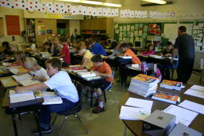 by: Photo By Susan Matheny - Culver teacher Daryl Ivie and students in one of the crowded third grade rooms.