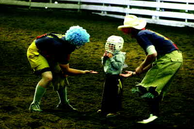 by: Photo By Gary Lindberg - A rodeo clown congratulates Riley Forman following a ride.