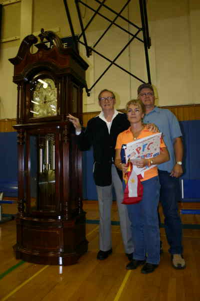 by: Photo By Susan Matheny - Carl Robinson of Arizona, at left, presented a Ridgeway grandfather clock to Wes and Meg Tucker last week in honor of their son Pfc. Tom Tucker.