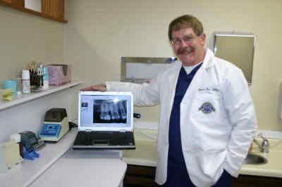 by: Photo By Susan Matheny - Dr. James Row shows how new digital X-rays can be enhanced on a computer screen for better diagnosis.