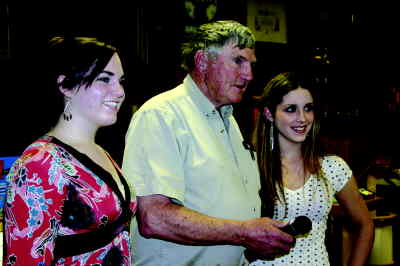by: Photo By Holly Gill - Elks member Jack Alley introduces Madras High scholarship winners Melissa Preston, left, and Kelsey Gill at the Ron DuRette pig roast fund-raiser.