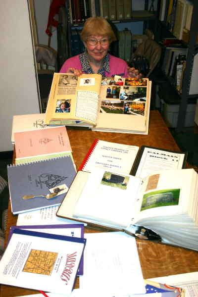 by: Photo By Susan Matheny - Beth Crow shows some of the history booklets the group has compiled.