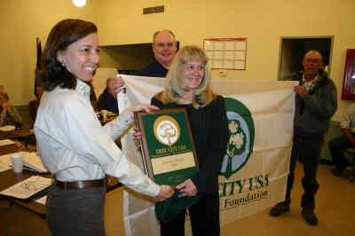 by: Photo By Holly M. Gill - Katie Lompa, left, from the Oregon Department of Forestry, presents a Tree City USA plaque to Metolius Mayor Sandy Toms.  Barry Davidson and Hal Littlejohn hold flag.