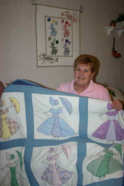 by: Photo By Susan Matheny - Claudia Minor with her mother's Sun Bonnet Sue quilt.
