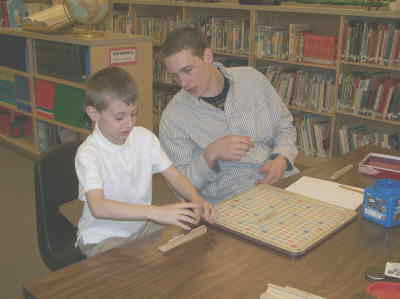 by: Submitted Photo - Jeremiah, left, gets some help from Big Brother Tyler Warren while playing a game of Scrabble in the Culver Elementary Library.