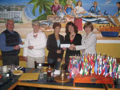 by: Submitted Photo - From left, Rotary member Dick Anderson presents check to Margee O'Brien for the food bank, and Rotary president Meredith Junge, far right, presents a check to Jennifer Anderson and Leanne Johnson of the Sparrow Clubs of Central Oregon.