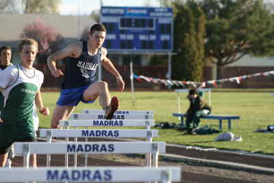 by: Photo By Gary Lindberg - Kelby MIlls had a lead early in the 300-meter hurdles race in Madras' IMC dual against Summit.