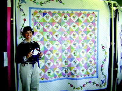 by: Aubmitted Photo - Mari Wymore stands by her Spring Fever quilt which won the People's Choice award at the quilt show.