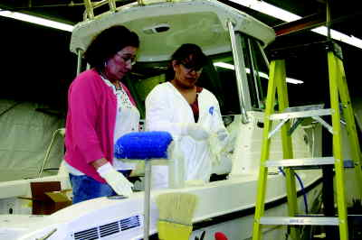 by: Photo By Holly M. Gill - Apolinar Downing, left, of Metolius, and Abigail Vega, of Culver, prepare to clean the last boat built at the Culver Seaswirl plant. This is the final week for most employees.