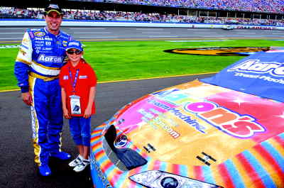 by: Submitted photo - Before the race at theTalladega Superspeedway, Marina Sansom, 9, of Madras, meets with racecar driver David Reutimann. Sansom's winning color design was featured on the Aaron's Dream Machine in the Busch Series Race.