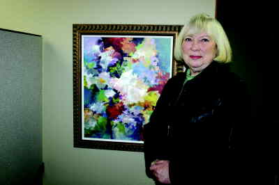 by: Photo By Susan Matheny - Metolius artist Nancy Goodenow with one of her colorful works.