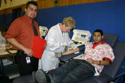 by: Photo By Susan Matheny - MHS graduate Ivan Gomez, left, the Red Cross collection operation supervisor for the drive, is shown with technician Jan Gilmore and junior Ismael Reynoso, a first-time donor.