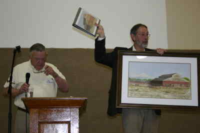 by: Photo By Susan Matheny - Auctioneer Ron McDonald consults his notes as helper Steve Rankin holds up a watercolor painting by Nita Carnagy of the old Madras Auction Yard, which sold for $440.