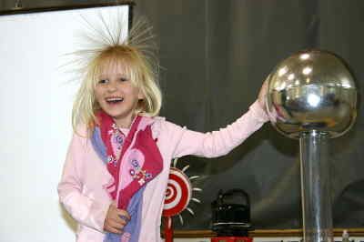 by: Photo By Susan Matheny - Metolius Elementary kindergartener Madison McCool had a bad hair day after touching the Van de Graff static machine during an OMSI assembly last Wednesday. Students were enlisted to help demonstrate ways to generate electricty.