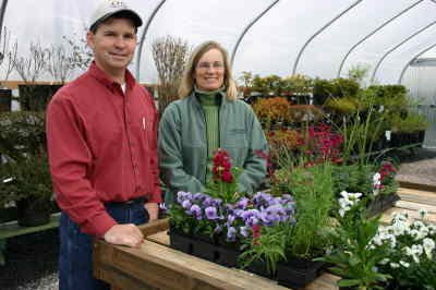 by: Photo By Susan Matheny - CHS Garden Center manager Scott Duggan and landscape designer Karen McCarthy in the center's greenhouse. The center, which held its grand opening April 19, features a large rock fountain and several demonstration gardens.