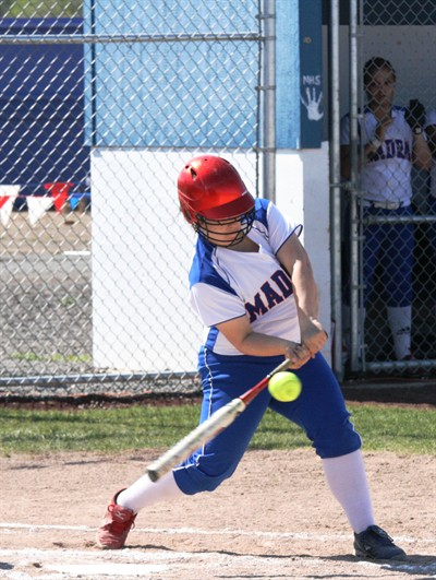 by: Photo By Joe McHaney - Alex Holcomb of Madras blasted a two-run game-winning home run at Sutherlin Wednesday to lift the White Buffalo softball team into the quarterfinals with a 4-2 victory over the Bulldogs.