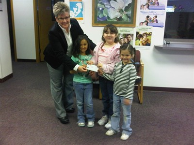 by: Submitted Photo - Jennifer Kimble accepts a donation from members of Madras Daisy Girl Scout Troop No. 50835.