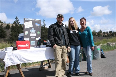 by: Photo by Joe McHaney - From left, Brandon Dubisar, of Madras, and Deidre Coen and Linda Newland, both of Bend, COCC team members, handed out gift certificates to cleanup volunteers.