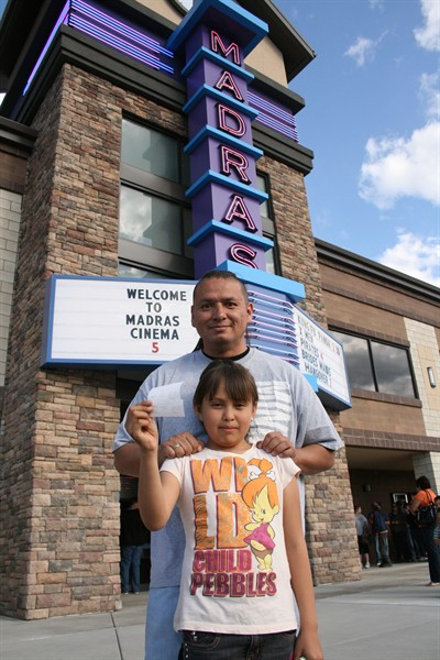 by: Photo by Joe McHaney - Frank Brunoe and his daughter Catherine Payenna, 10, who's holding their tickets, were the first in line to buy tickets when the Madras Cinema 5 opened June 3.
