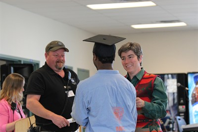 by: Photo by Holly M. Gill - Tucker Bauman, welding director at DRCI, and Dr. Cody Yeager, COCC director of education for Deer Ridge, congratulate an inmate at a graduation ceremony June 3.