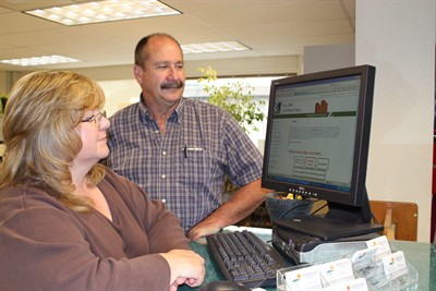 by: Photo by Holly M. Gill - Rena Thompson, administrative supervisor for the Jefferson County Community Development Department, and Chet Singleton, county building official, demonstrate the convenient new website for permits.