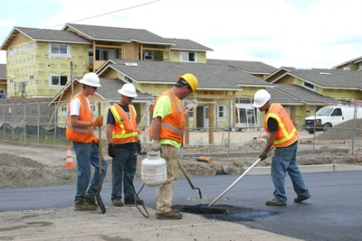 by: Photo by Holly M. Gill - On Friday,  a crew from 7 Peaks Paving, of Bend, finished up the paving on a section of Jefferson Street in front of the Canyon East Apartments. The apartments, for low-income farm workers, should be finished in August.