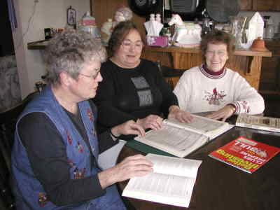 by: Photo By Susan Matheny - Investment club members Marilyn Brown, left, Lillian January and Mary K. Irwin use many resources to track stock.